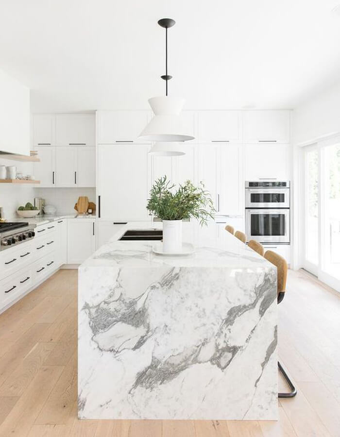 White/grey marbled countertop with built-in sink on matching island